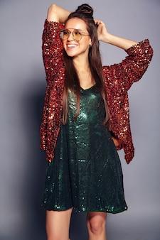 Schönes kaukasisches lächelndes hipster-brünettenfrauenmodell in der hellen glänzenden reflektierenden sommerlichen stilvollen jacke und im grünen kleid, die auf grau aufwerfen