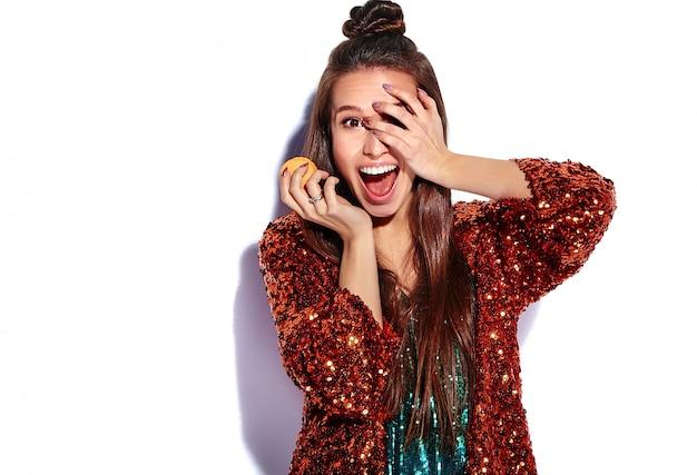 Schönes kaukasisches lächelndes hipster-brünettenfrauenmodell in der hellen glänzenden reflektierenden sommerlichen stilvollen jacke und im grünen kleid lokalisiert. französische makrone essen