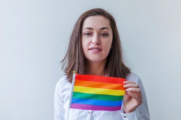 Schönes kaukasisches lesbisches mädchen mit lgbt-regenbogenfahne lokalisiert auf weiß