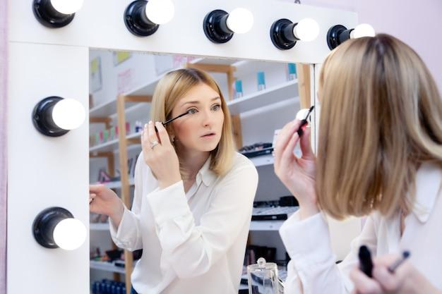 Schönes kaukasisches mädchen bilden künstler, visagiste, vorbildlichen blick auf reflexion im spiegel mit lampen und dem auftragen der schwarzen peitschenwimperntusche. anzeige keine marke dekorative professionelle kosmetikgeschäft