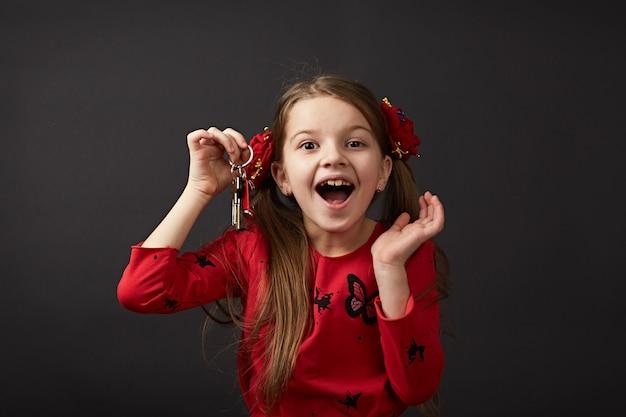 Schönes kaukasisches mädchen, das autoschlüssel, wohnung hält. ein kind in roten kleidern ist sehr glücklich