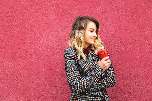 Schönes kaukasisches mädchen, das ein gelbes herbstblatt und einen roten tasse kaffee stehen nahe der roten wand hält.