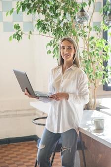 Schönes kaukasisches mädchen, das einen laptop in ihren händen im büro hält.