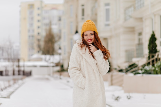 Schönes kaukasisches mädchen, das im wintertag durch stadt geht. frohe ingwerfrau im weißen kittel, der auf der straße aufwirft.