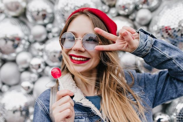 Schönes kaukasisches mädchen, das süßigkeiten mit lächeln auf funkelnder wand isst. charmante blonde frau posiert mit lutscher in der nähe von discokugeln.