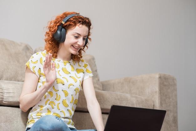 Schönes kaukasisches mädchen, das zu hause auf dem boden auf dem teppich sitzt und einen laptop benutzt. arbeiten im internet. gruß