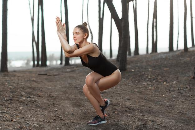 Schönes kaukasisches mädchen in einem schwarzen badeanzug führt eine schwierige haltung im yoga durch