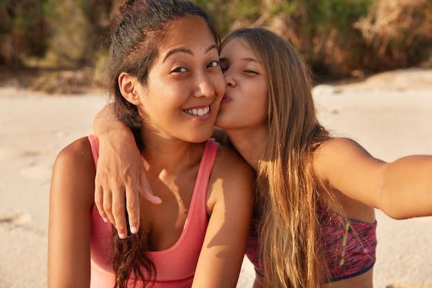 Schönes kaukasisches mädchen küsst in wange ihre freundin
