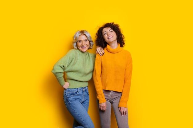 Schönes kaukasisches mädchen mit dem lockigen schwarzen haar, das mit ihrem blonden freund auf gelbem hintergrund aufwirft