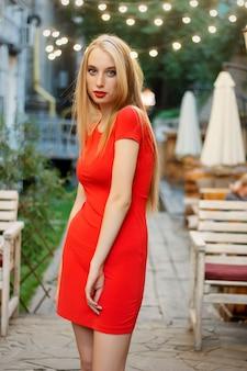 Schönes kaukasisches mädchen mit rotem lippenmake-up in einem restaurant. schöne sexy blonde frau im verführerischen mädchen des restaurantcafés in der roten kleiderfrisur und im make-up, das nachtisch isst. schlankes modell der schönheitsmode