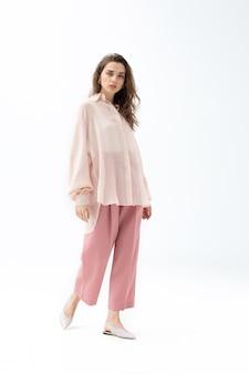 Schönes kaukasisches modell, das im insgesamt rosa kleid aufwirft