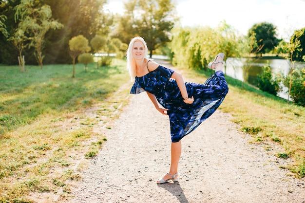 Schönes kaukasisches modell, das wie ballerina im sommerpark aufwirft