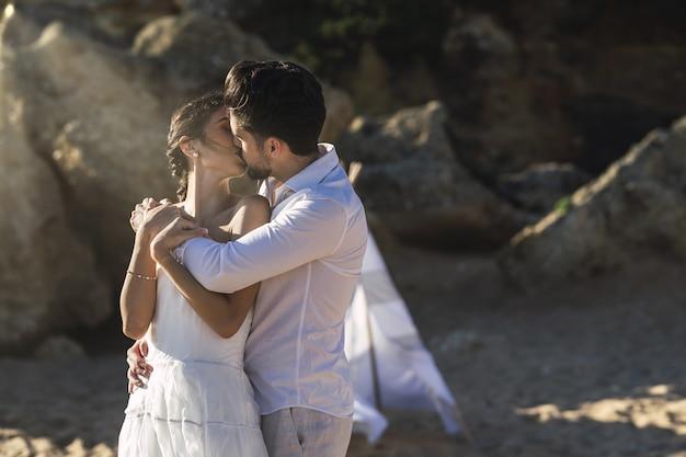 Schönes kaukasisches paar, das am strand küsst