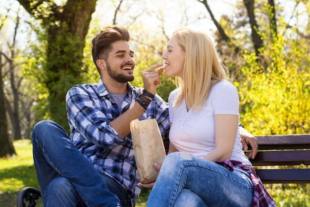 Schönes kaukasisches paar, das auf einer parkbank sitzt