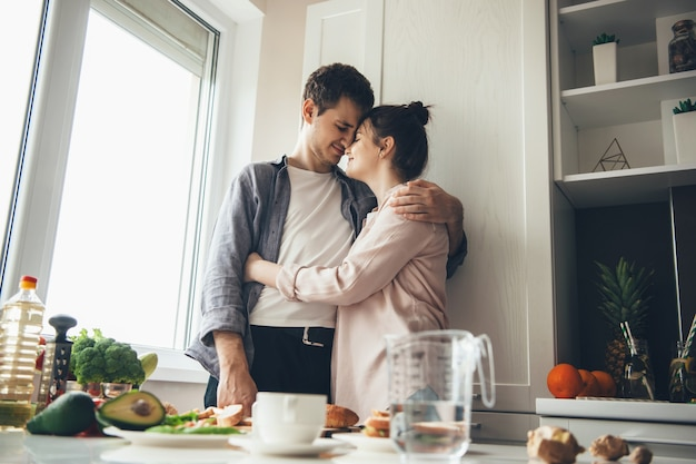 Schönes kaukasisches paar in der küche umarmend, während essen zusammen vorbereiten