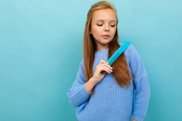 Schönes kaukasisches teenager-mädchen mit braunen haaren im blauen kapuzenpulli bürstet ihr haar lokalisiert auf blau