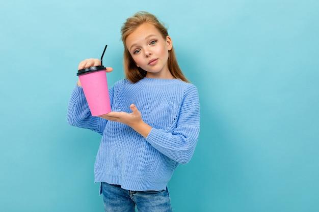 Schönes kaukasisches teenager-mädchen mit braunen haaren im blauen kapuzenpulli trinkt kaffee mit rosa tasse lokalisiert auf blau