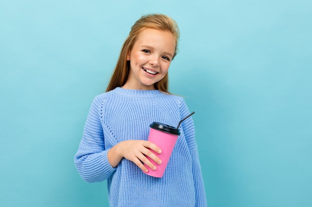 Schönes kaukasisches teenager-mädchen mit braunen haaren im blauen kapuzenpulli trinkt kaffee mit rosa tasse lokalisiert auf blauem hintergrund