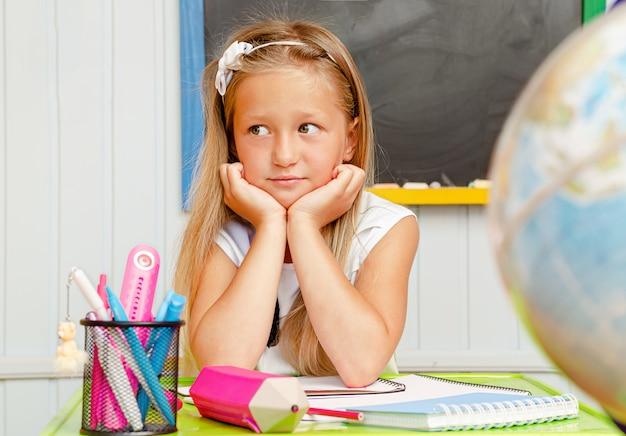 Schönes kaukasisches vorschulkind, das im unterricht gelangweilt ist.