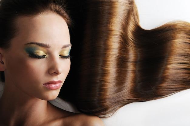 Schönes kaukasisches weibliches gesicht mit langen üppigen haaren - geschlossene augen