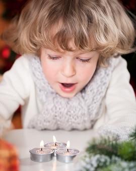 Schönes kind, das brennende weihnachtskerzen ausbläst. fokus auf kerzen