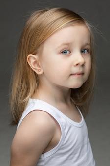 Schönes kind, das eine unterwäsche trägt, die ruhig schaut, während auf grauem hintergrund stehend. kindheitskonzept