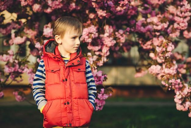 Schönes kind in modekleidung auf einem spaziergang im frühling. glückliche und gesunde kindheit