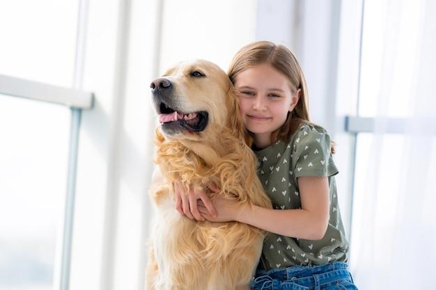 Schönes kind mädchen umarmt golden retriever hund und lächelnd drinnen kind streichelt reinrassiges hündchen haustier...