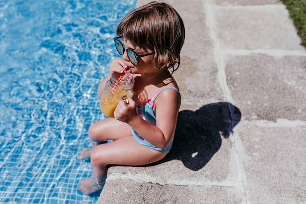 Schönes kindermädchen am pool, das gesunden orangensaft trinkt und spaß im freien hat. sommer- und lifestyle-konzept