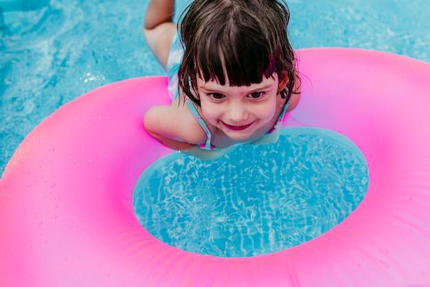 Schönes kindermädchen, das auf rosa donuts in einem pool schwimmt. lächelnd. spaß und sommerlicher lebensstil