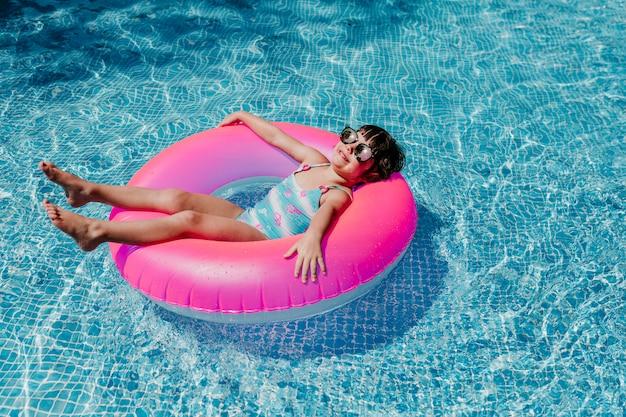 Schönes kindermädchen, das auf rosa donuts in einem pool schwimmt. sonnenbrille tragen und lächeln. spaß und sommerlicher lebensstil