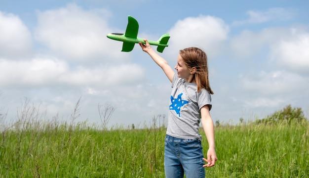 Schönes kindermädchen, das mit grünem spielzeugflugzeug draußen im feld spielt, jugendliches kind, das airpla startet ...