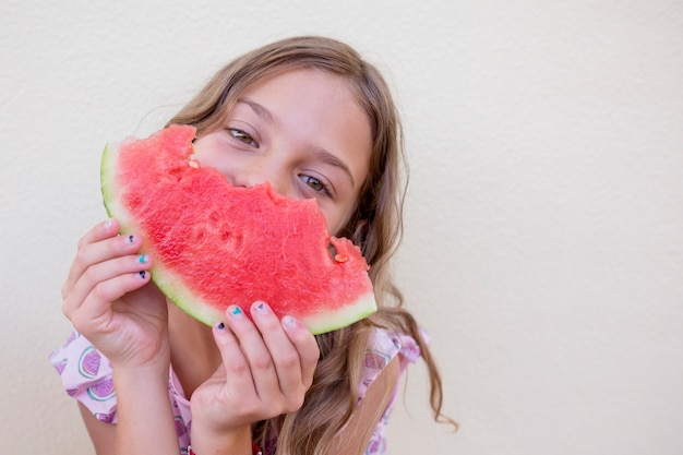 Schönes kindermädchen, das wassermelone über weißer wand isst. familienliebe und lebensstil im freien
