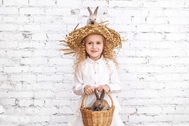 Schönes kindermädchen mit lockigem haar und flauschigen kaninchentieren, die auf einem hut sitzen