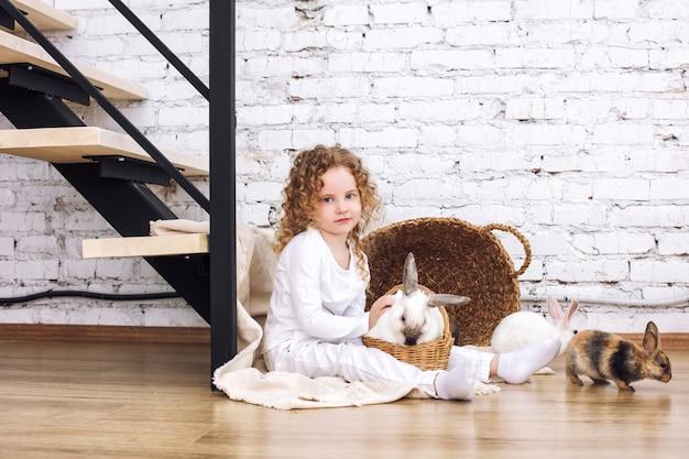 Schönes kindermädchen mit lockigem haar und mit flauschigen kaninchentieren zu hause in weißem interieur