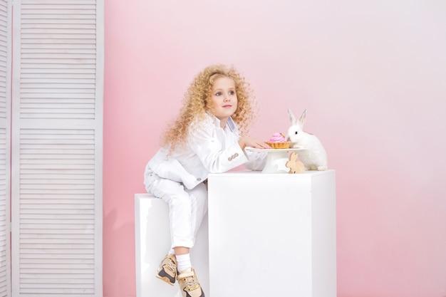 Schönes kindermädchen mit lockigem haar und mit flauschigen tierkaninchen auf rosa hintergrund