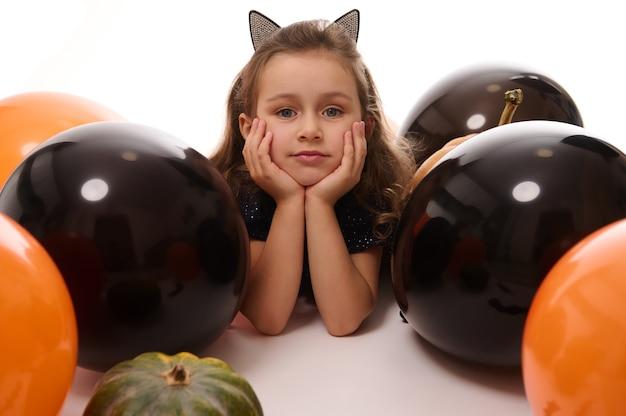 Schönes kindermädchen mit reifen mit katzenohren betrachtet die kamera, die sich neben kürbis, farbigen schwarzen und orangefarbenen ballons auf weißem hintergrund mit kopienraum hinlegt. halloween-konzept
