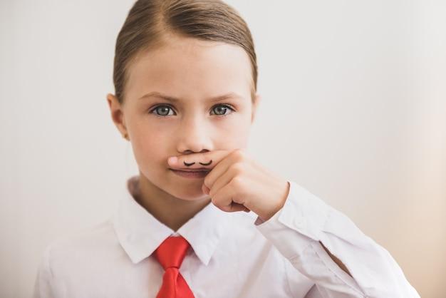 Schönes kindermädchen zeigt gemalten schnurrbart. feminismus-konzept