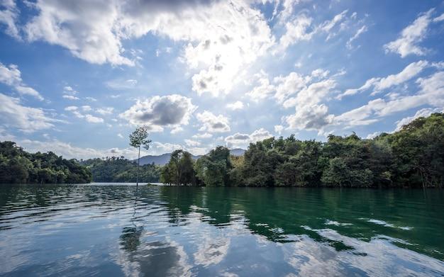 Schönes klares wasser bei cheow lan lake mit morgenlicht, reflexion des blauen himmels