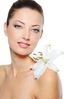 Schönes klares weibliches gesicht mit gesunder haut und weißer lilie auf ihrer schulter