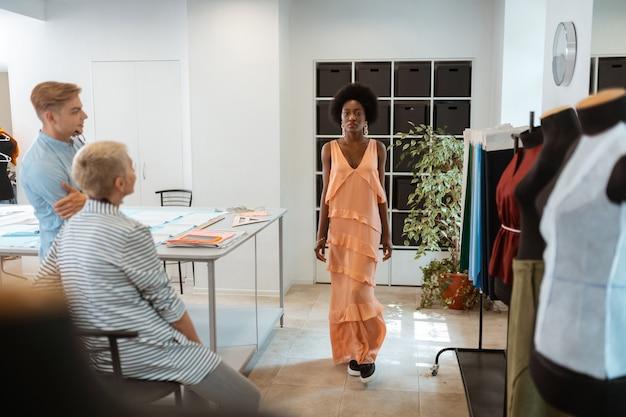 Schönes kleid. hübsches afroamerikanisches mädchen, das ein schönes kleid und stylische schwarze turnschuhe trägt