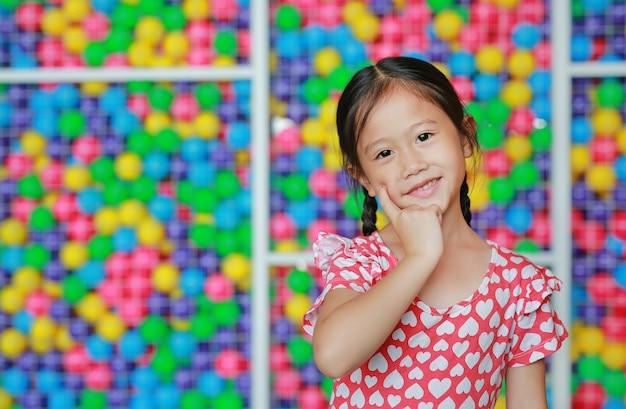 Schönes kleines asiatisches kindermädchen, das zeigefinger auf backe gegen bunten spielzeugballspielplatz hält