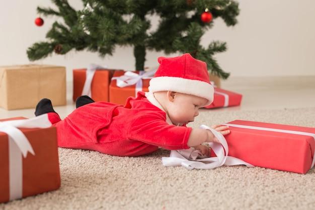Schönes kleines baby feiert weihnachten. neujahrsfeiertage. baby in einem weihnachtskostüm und in weihnachtsmütze und geschenkbox.