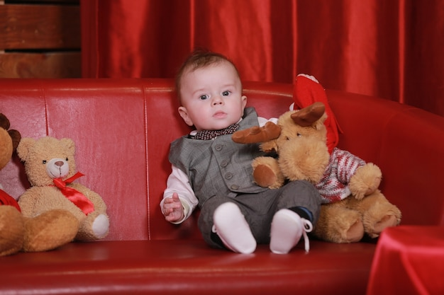 Schönes kleines baby feiert weihnachten. neujahrsfeiertage. baby mit geschenk.