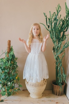 Schönes kleines blondes langhaariges kindermädchen im weißen kleid, das im tongefäß zwischen zwei grünpflanzen steht