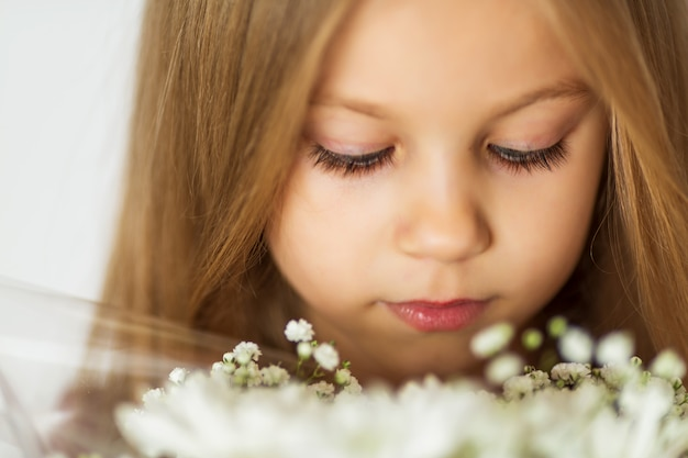 Schönes kleines blondes mädchen mit einem blumenstrauß von wildflowers