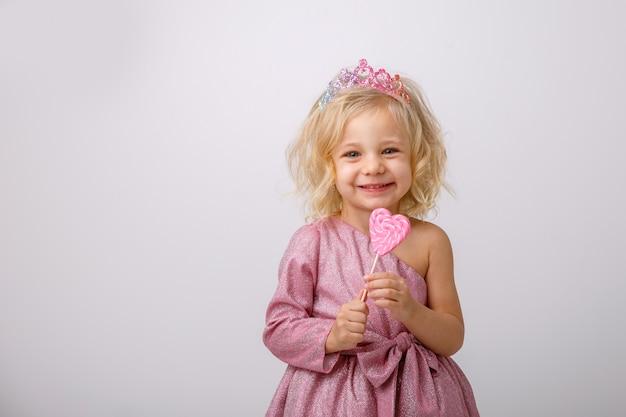 Schönes kleines blondes mädchen mit einem herzen formte lutscher