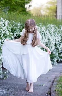 Schönes kleines blondes mädchen von 9 jahren, mit langen haaren in einem weißen seidenkleid, tanzendem ballett im park, blick nach unten, ihr kopf hat viele kleine weiße blütenblätter
