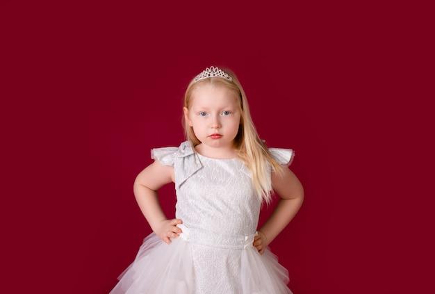 Schönes kleines blondes prinzessintanzen im weißen und silbernen luxuskleid lokalisiert auf rotem hintergrund. lustiges gesicht, verschiedene emotionen