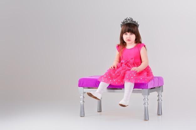 Schönes kleines brünettes mädchen im rosa prinzessinkleid mit krone, die auf einem rosa stuhl auf grauem hintergrund sitzt. süßes baby